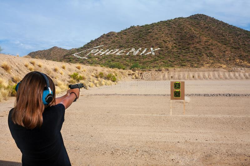 Preteen Girl Shooting a 9mm Pistol at a Shooting Range Near Phoenix Arizona. Preteen girl shoots a 9mm pistol at a shooting range near Phoenix, Arizona.  There stock photo