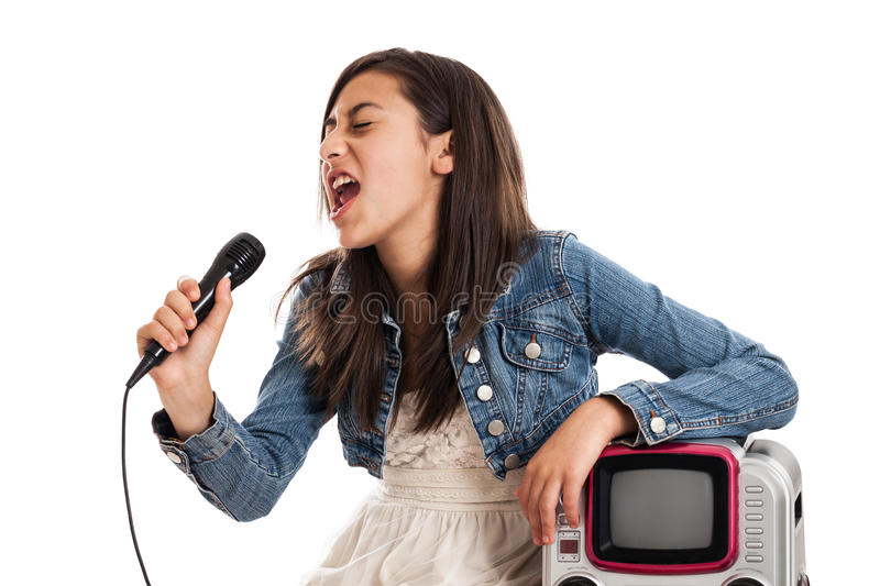 Preteen girl singing karaoke. A mixed race preteen girl singing karaoke with a microphone isolated on white stock photo