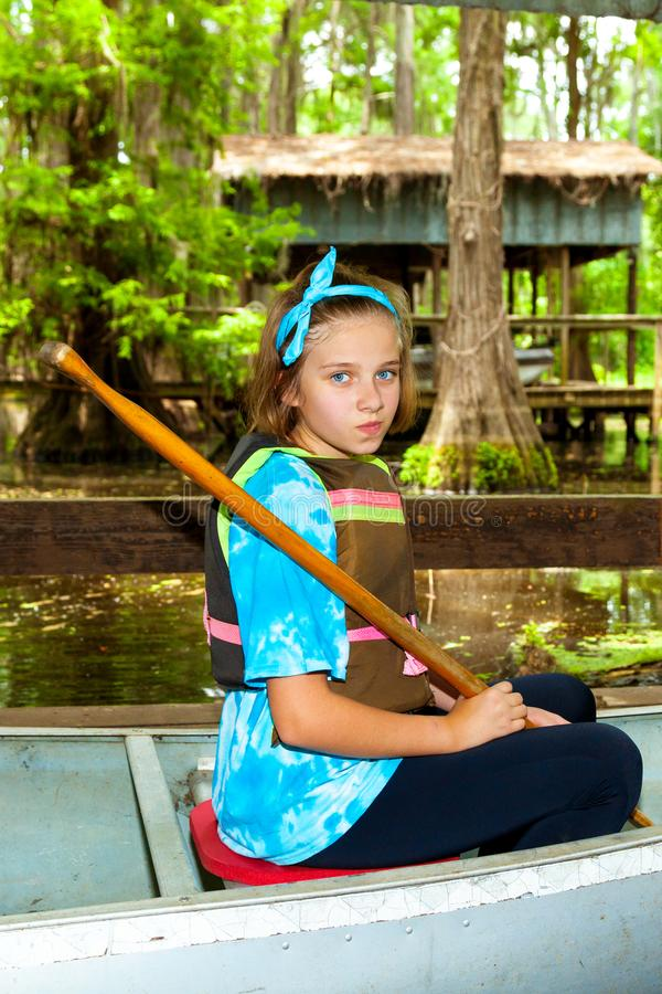 PreTeen Girl Sits in a Metal Canoe Ready to Launch with Paddle i royalty free stock photography