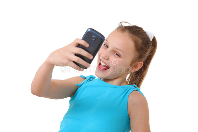 Preteen girl taking self-portrait with mobile phone royalty free stock photos