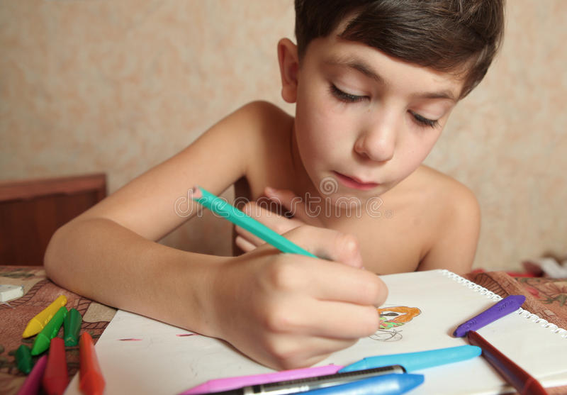 Preteen handsome boy with crayons stock photo