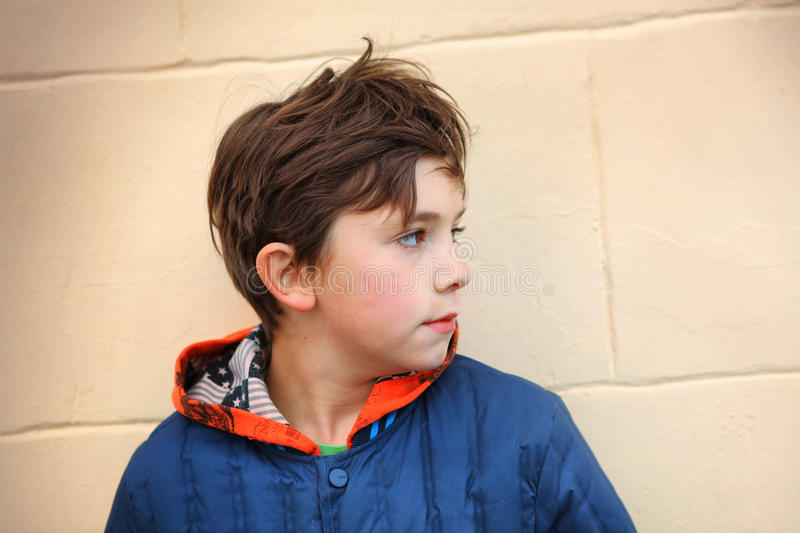 Preteen handsome boy half face close up portrait. On the beige wall background royalty free stock images