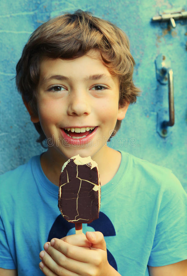 Preteen handsome boy with sun tan and escimo icecream. Close up portrait on the blue door background stock images