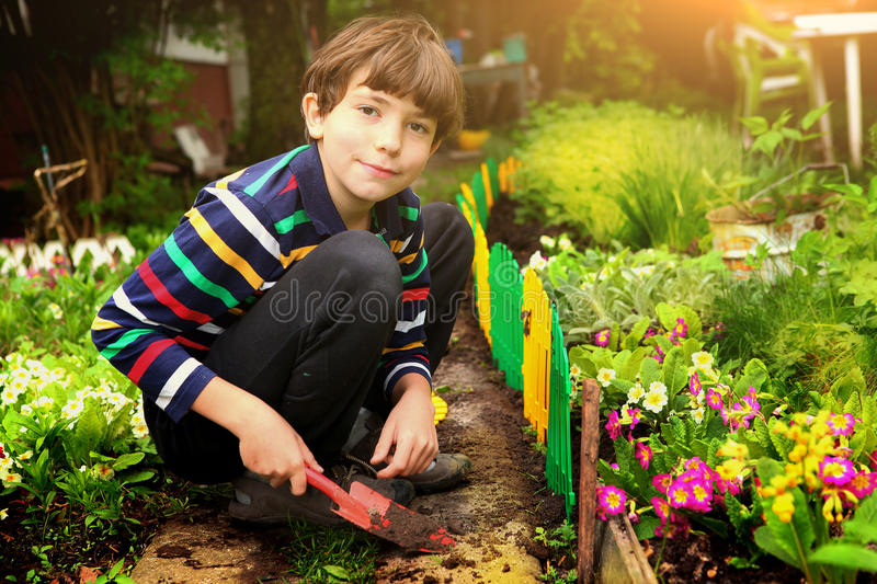 Preteen handsome boy work in the garden. Preteen handsome boy work in the blossoming summer garden royalty free stock image