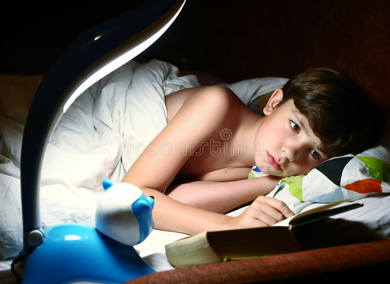 Preteen knap jongen gelezen boek vóór slaap royalty-vrije stock afbeeldingen