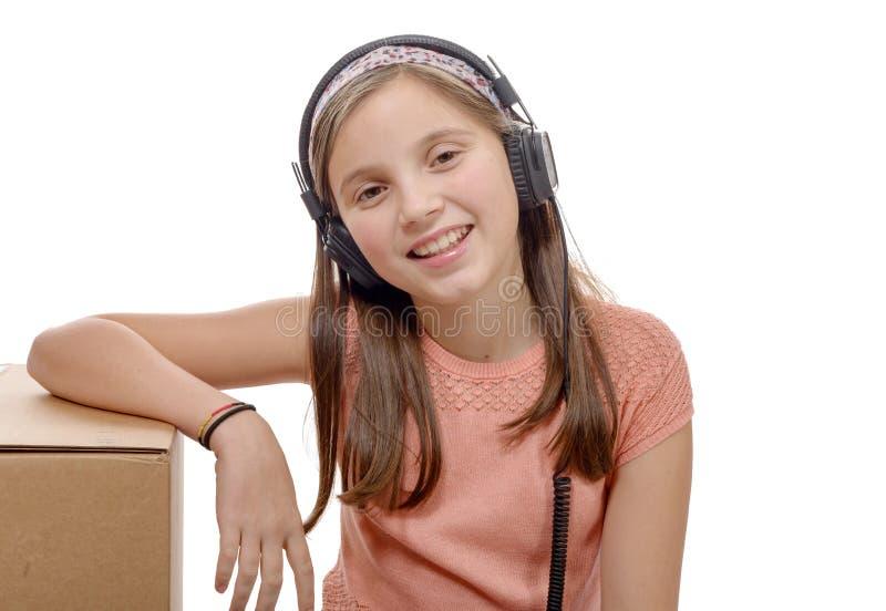 Preteen que escuta a música com os fones de ouvido no branco foto de stock royalty free