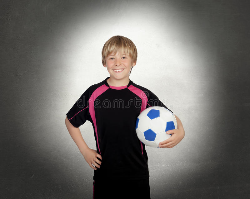 Preteen with a uniform for play soccer holding a ball stock image