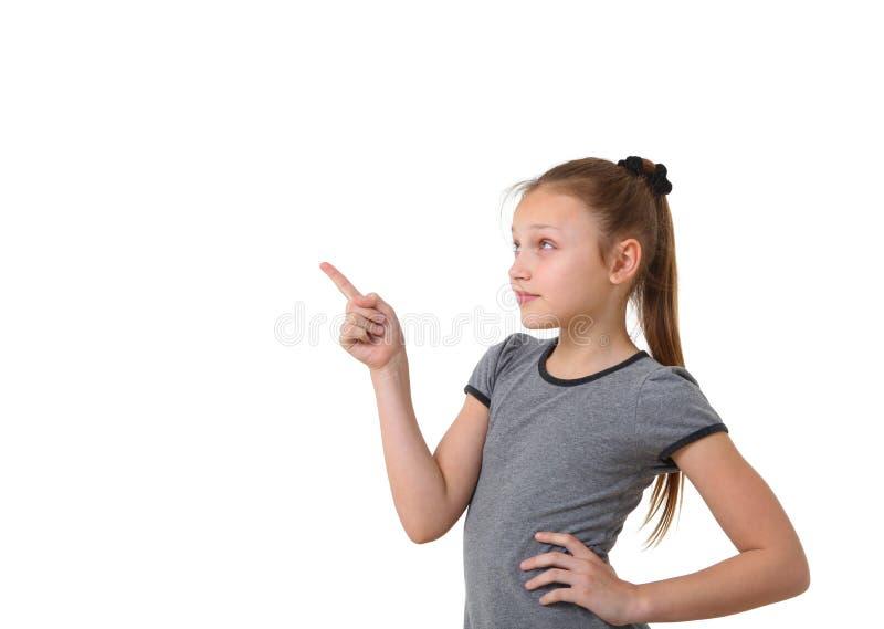 Preteenflicka som pekar på kopieringsutrymmet arkivfoton