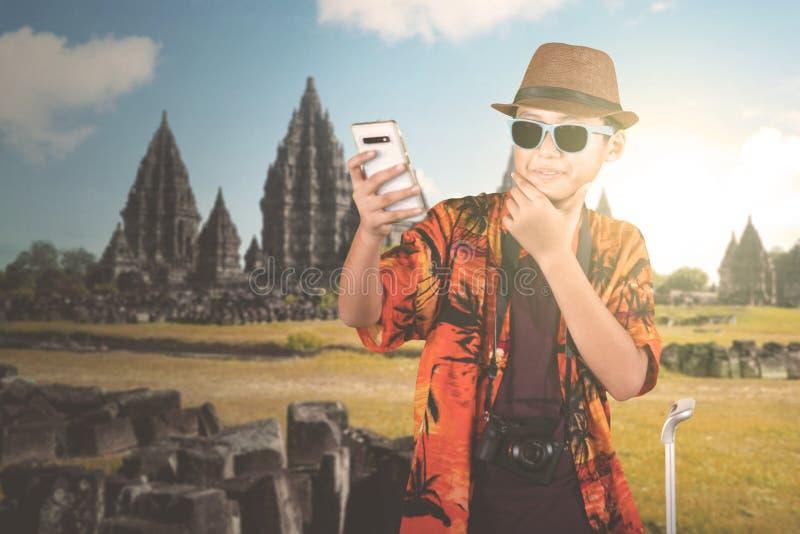 Preteenjongen die foto nemen dichtbij Prambanan-tempel stock afbeeldingen
