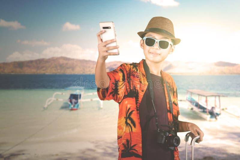 Preteenjongen die foto's op het strand nemen royalty-vrije stock afbeeldingen