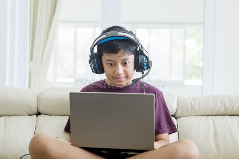 Preteenjongen die online spelen op laptop spelen stock afbeelding