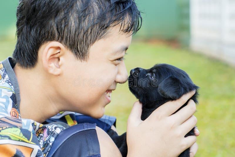 Preteenjongen die zijn puppy in het park kussen royalty-vrije stock fotografie