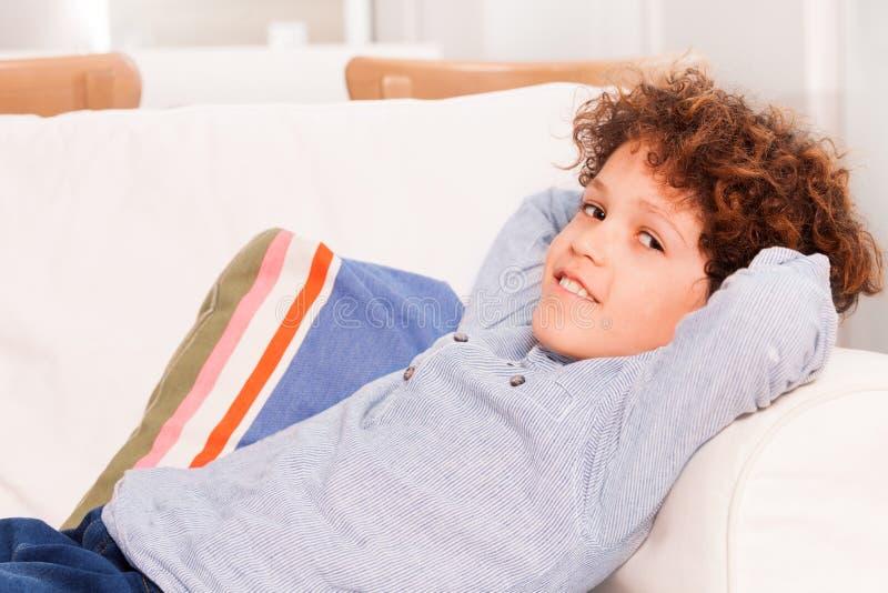 Preteenjongen het ontspannen op witte comfortabele bank stock afbeelding
