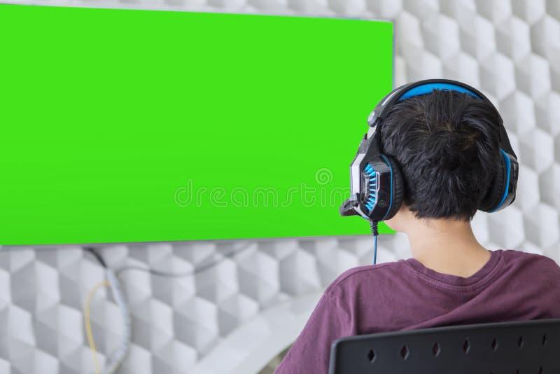 Preteenjongen het spelen videospelletje op een TV stock foto's