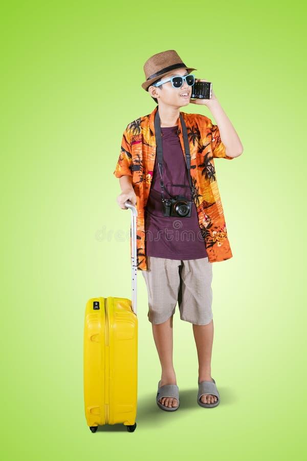 Preteenjongen met telefoon en bagage op studio royalty-vrije stock foto's