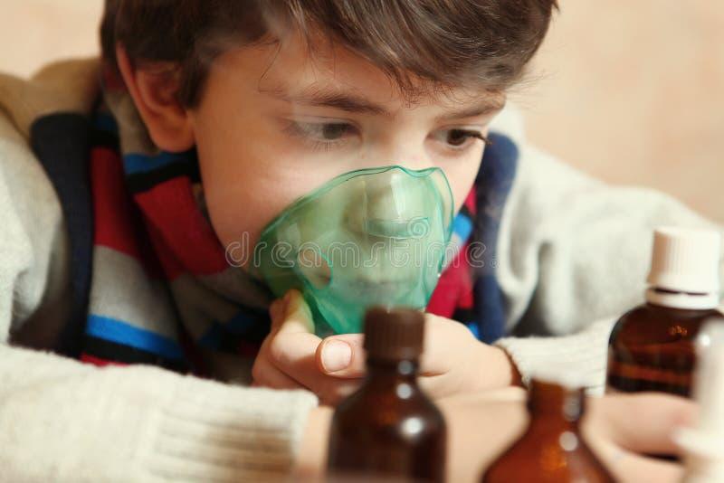 Preteenpojke med den elektriska inhalatorn arkivfoton