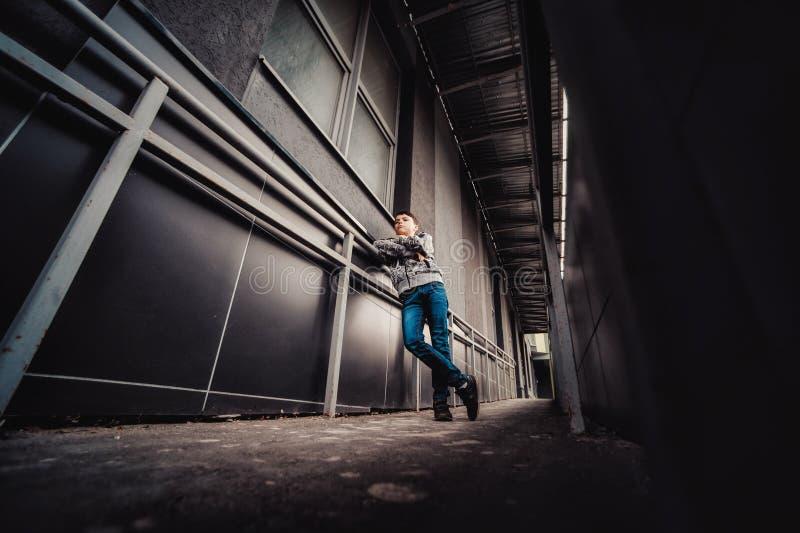 Preteenpojke på en gata i en storstad bredvid ett höghus bara royaltyfri fotografi