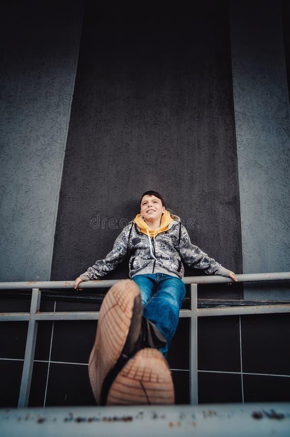 Preteenpojke på en gata i en storstad bredvid ett höghus bara royaltyfria bilder