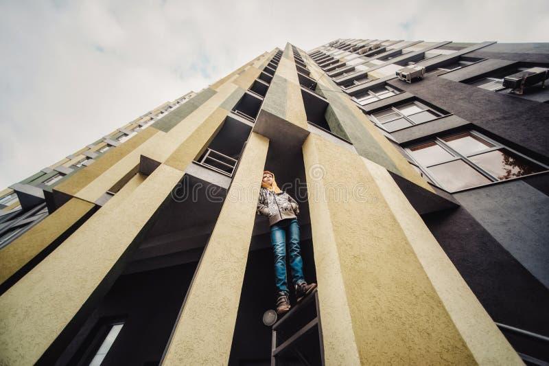 Preteenpojke på en gata i en storstad bredvid ett höghus bara arkivbild
