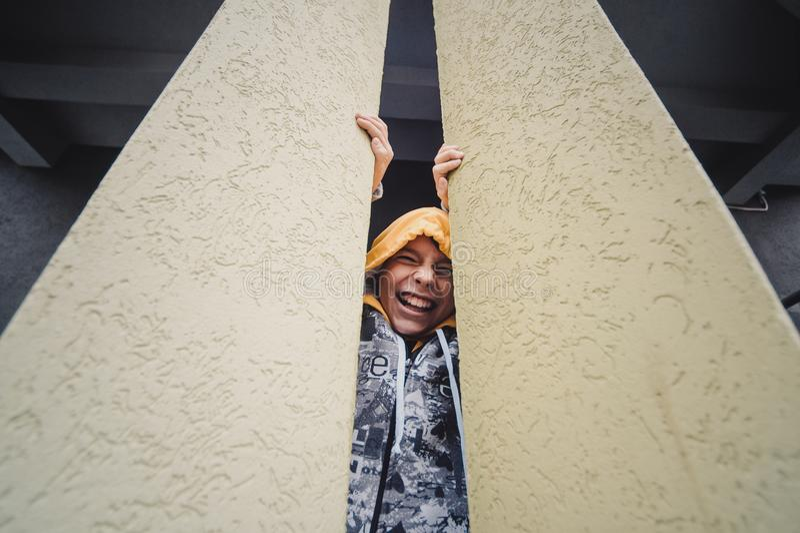 Preteenpojke på en gata i en storstad bredvid ett höghus bara fotografering för bildbyråer