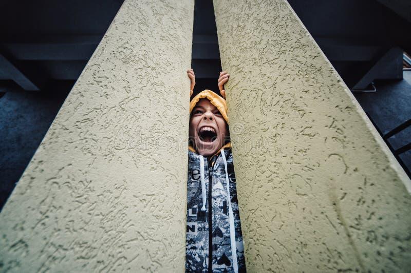 Preteenpojke på en gata i en storstad bredvid ett höghus bara arkivfoton