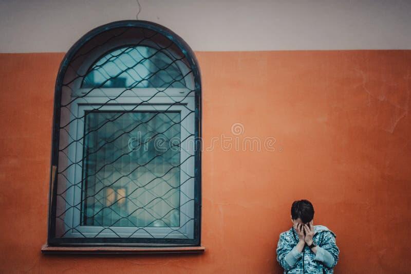 Preteenpojke på en gata i en storstad bredvid ett höghus bara royaltyfri bild