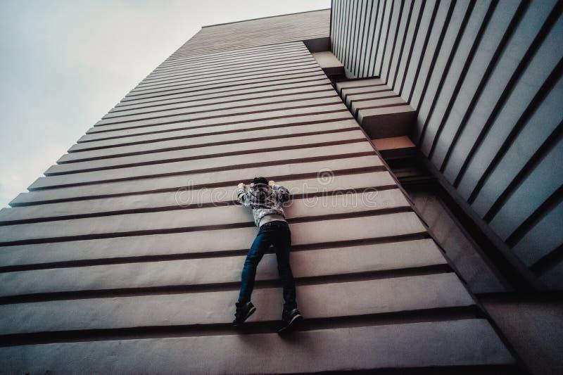 Preteenpojke på en gata i en storstad bredvid ett höghus bara royaltyfria foton