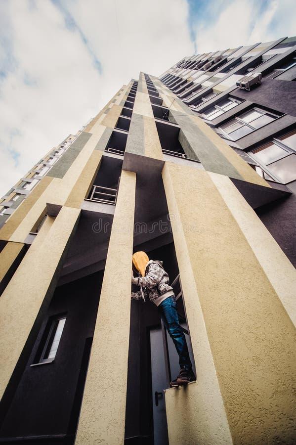 Preteenpojke på en gata i en storstad bredvid ett höghus bara royaltyfri foto