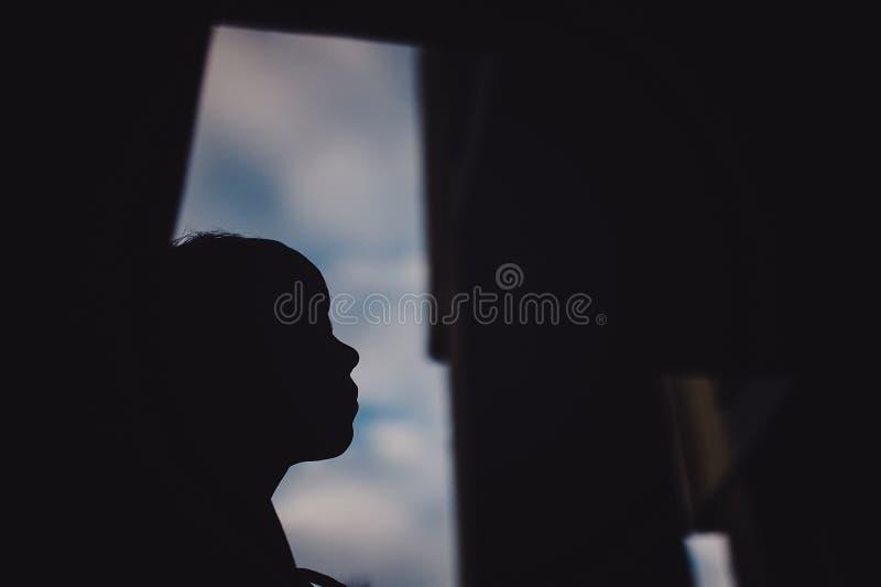 Preteenpojke på en gata i en storstad bredvid ett höghus bara arkivfoto