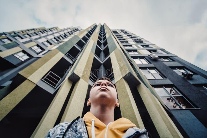 Preteenpojke på en gata i en storstad bredvid ett höghus bara arkivbilder