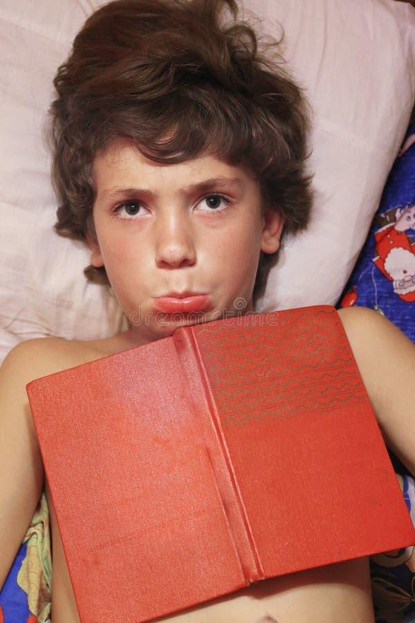 Preteenpojkeslut upp fotoet med boken i säng royaltyfri bild
