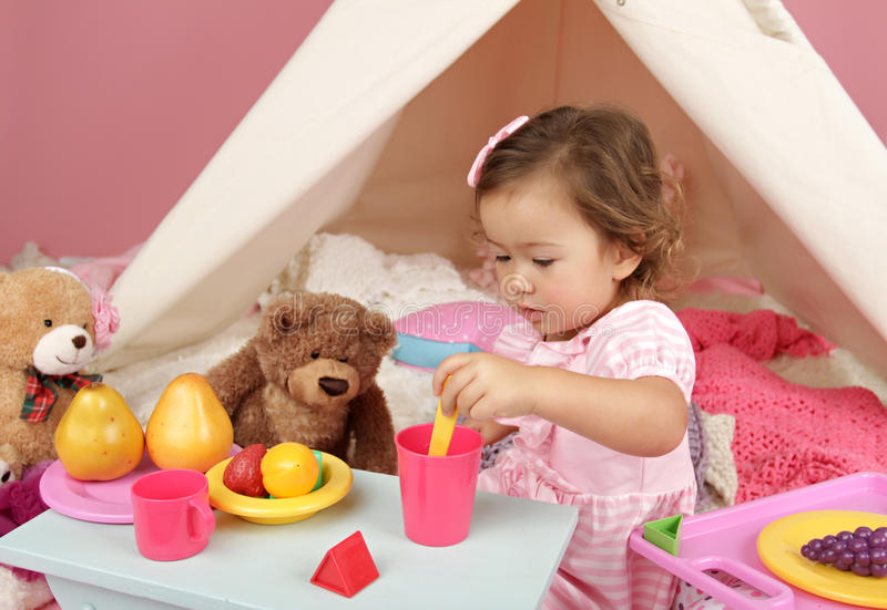 Pretend Play Tea Party at home with a TeePee Tent. Happy toddler girl engaged in pretend play tea party indoors at home with a teepee tent royalty free stock photography