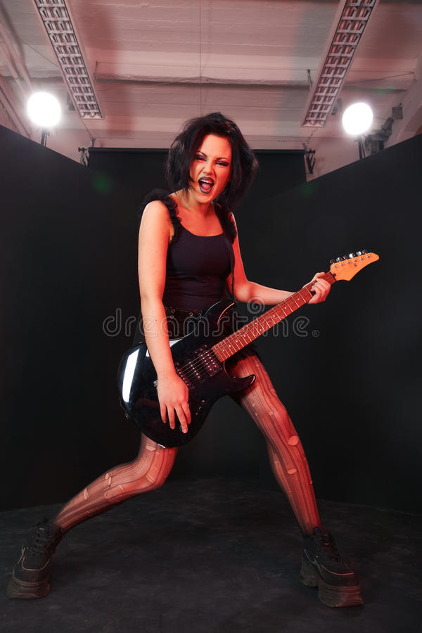 Pretending to be a rockstar. Young girl pretending to be a next rock superstar stock photography