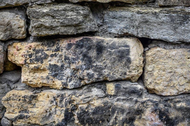 Preto e amarelo abstratos do fundo da parede da rocha fotografia de stock
