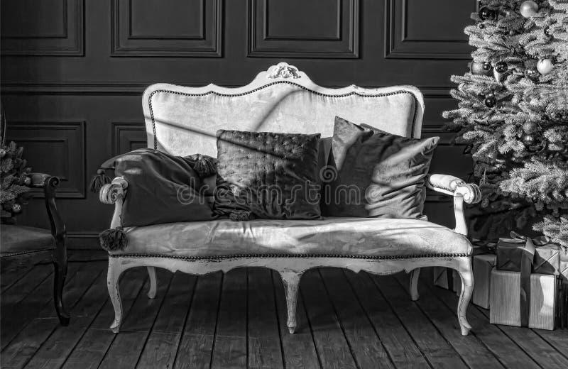 Preto e branco, árvore de Natal no interior real A sala de visitas de ano novo com o sofá branco à moda antigo com dourado luxuos foto de stock royalty free