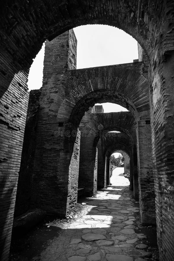 Preto e branco dos arcos romanos antigos que repetem sobre um caminho de pedra em Roma, Itália imagem de stock royalty free