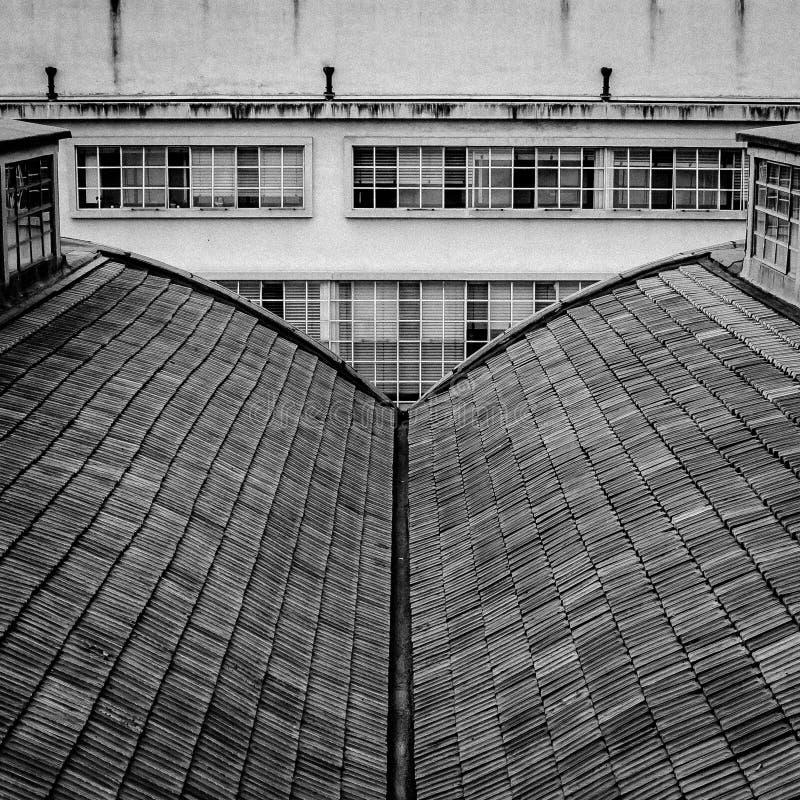 Preto e branco o telhado da construção olha como um livro aberto no fundo de uma outra construção industrial fotografia de stock