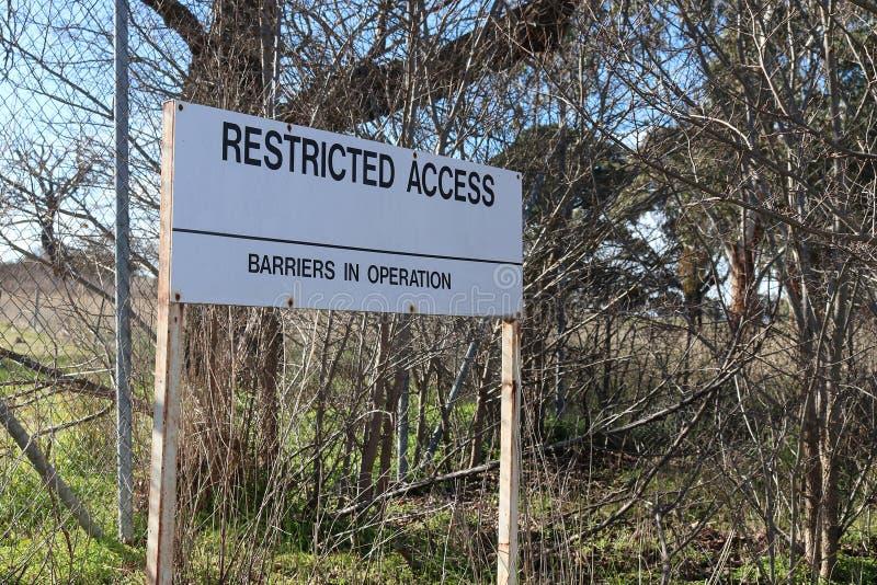 A preto e branco resistido restringiu o acesso, barreiras no sinal de aviso da operação foto de stock