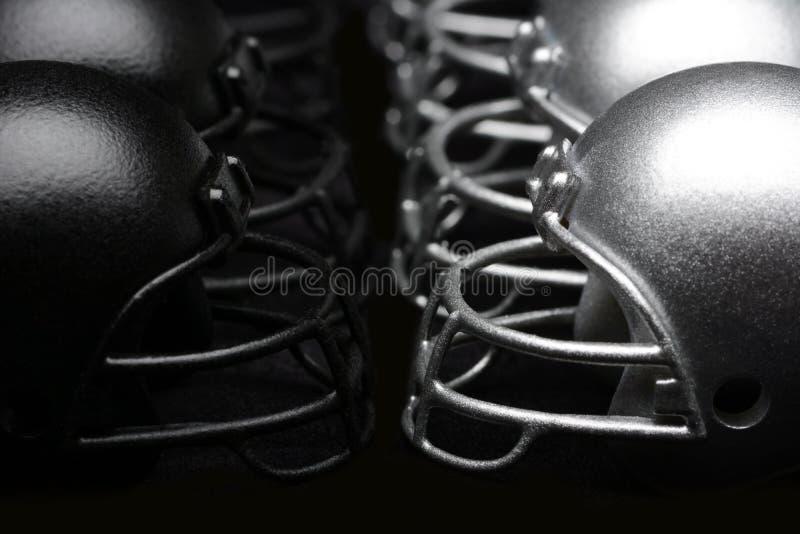 Preto e capacetes de futebol americano da prata alinhados fotografia de stock