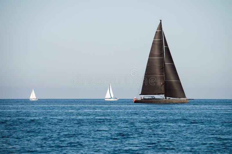 Preto e dois iate brancos da navigação no mar imagens de stock