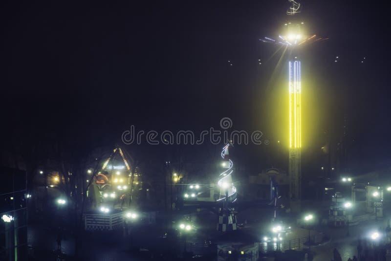 Pretpark bij nacht - bekijk van ferris wiel, carrousels en aantrekkelijkheden in motie stock afbeelding