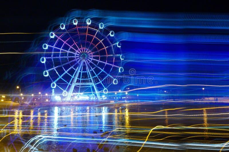 Pretpark bij nacht - de gloed van het Reuzenradneon in motie stock afbeeldingen