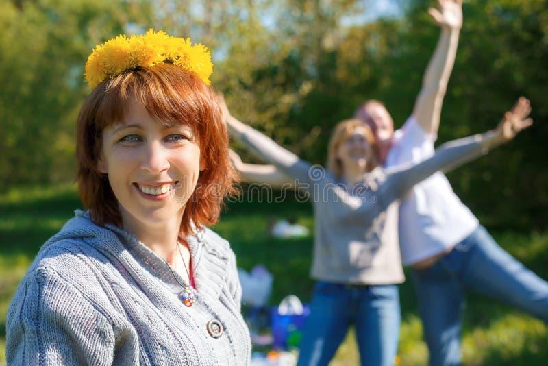 Pretpicknick met vrienden Een kroon van paardebloemen op zijn hoofd stock fotografie