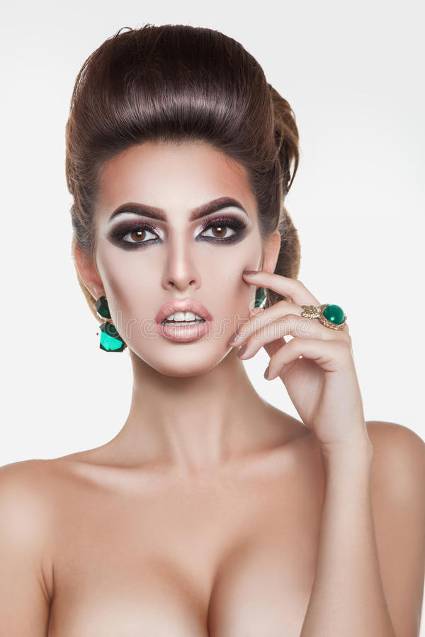 Prettiest brunette girl with green diamonds and creative hairsty royalty free stock image