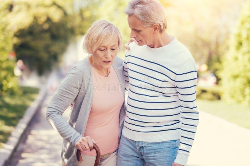 Prettig bejaarde die met haar echtgenoot lopen stock foto's