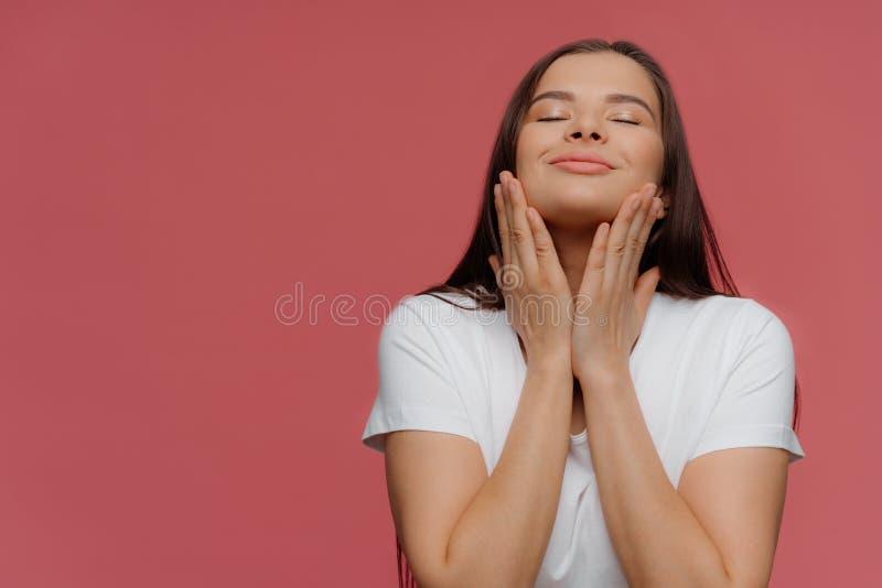 Prettig gevoel De opgetogen donkerbruine vrouw geniet van zachtheid van huid na kuuroordprocedures, raakt kin, houdt ogen geslote royalty-vrije stock foto's