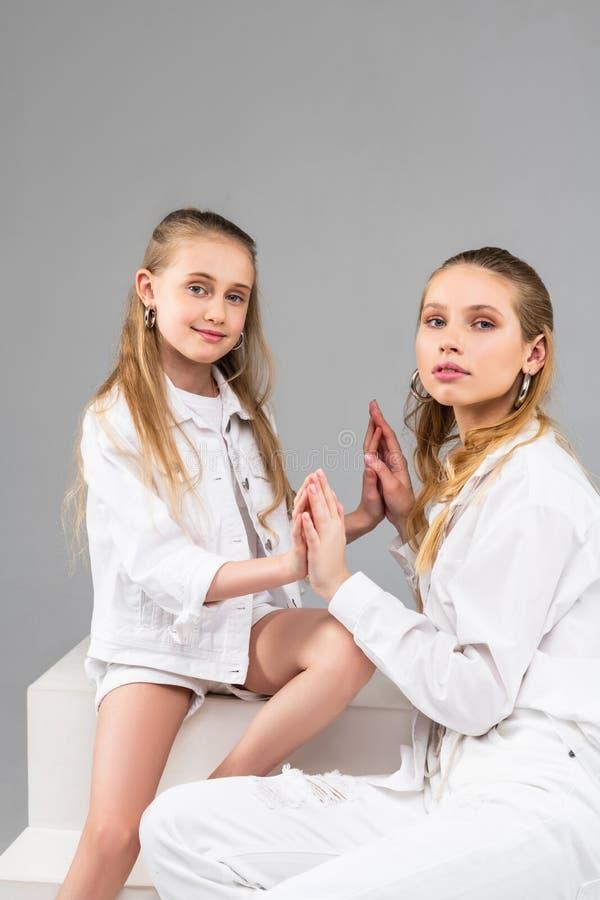 Prettig jong meisje in witte borrels en jasje die haar palmen vastmaken royalty-vrije stock afbeelding