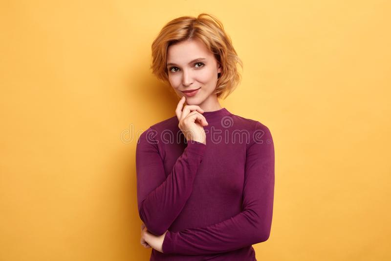 Prettig knap wijfje in in vrijetijdskleding met vinger op haar kin royalty-vrije stock foto