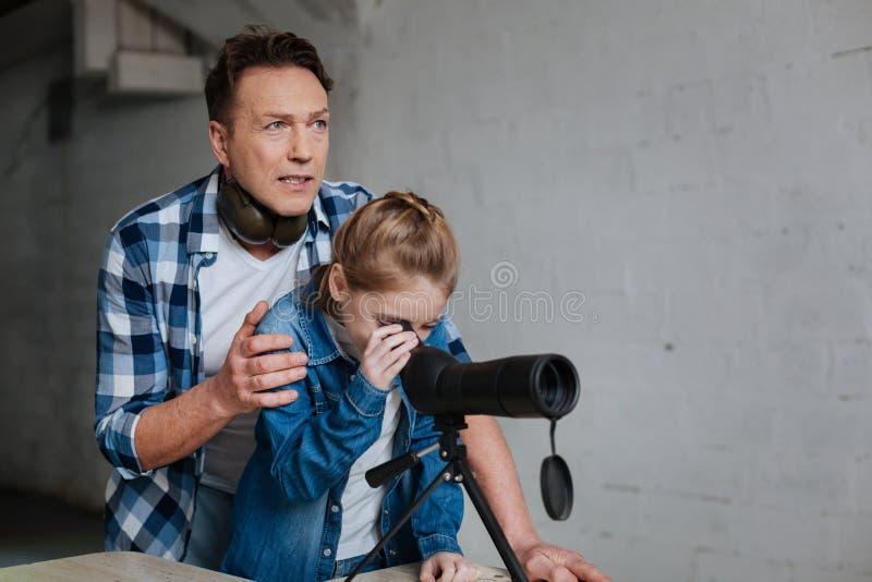 Prettig mooi meisje die de optische telescoop onderzoeken stock afbeelding