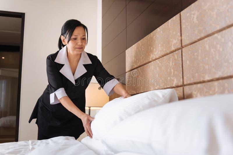 Prettig opgetogen hotelmeisje die het bed maken royalty-vrije stock afbeeldingen